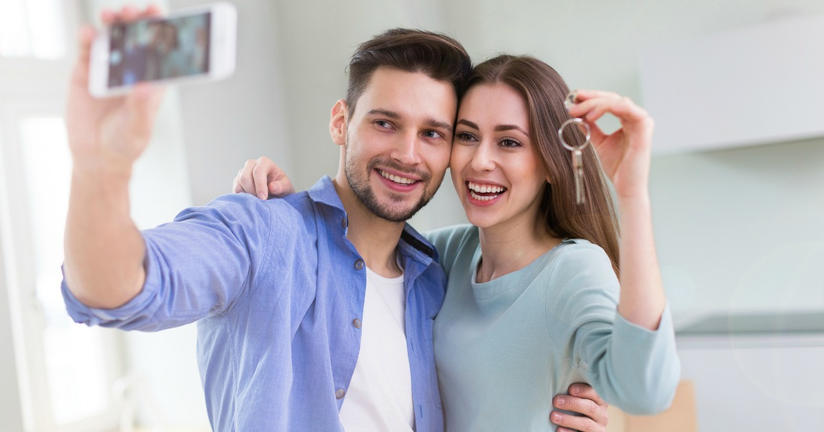 picture of new home buyers with a photo of their new house