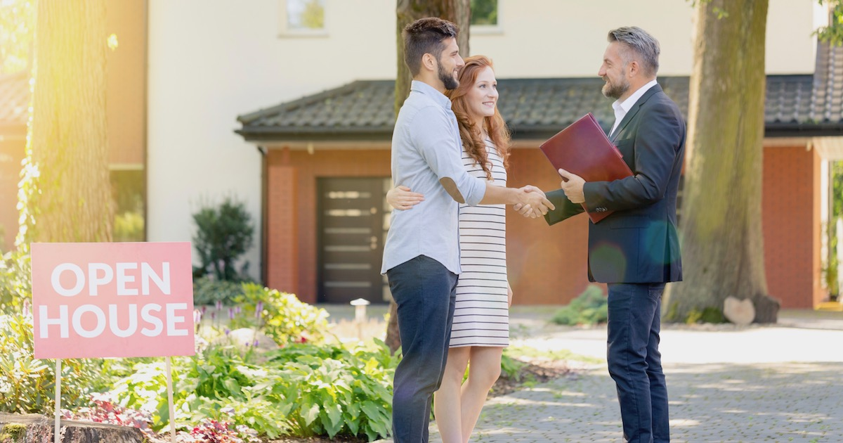 real estate agent greeting visitors during an open house